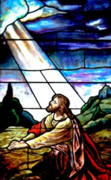 Stained glass image of Jesus looking towards the sky, light beaming down.